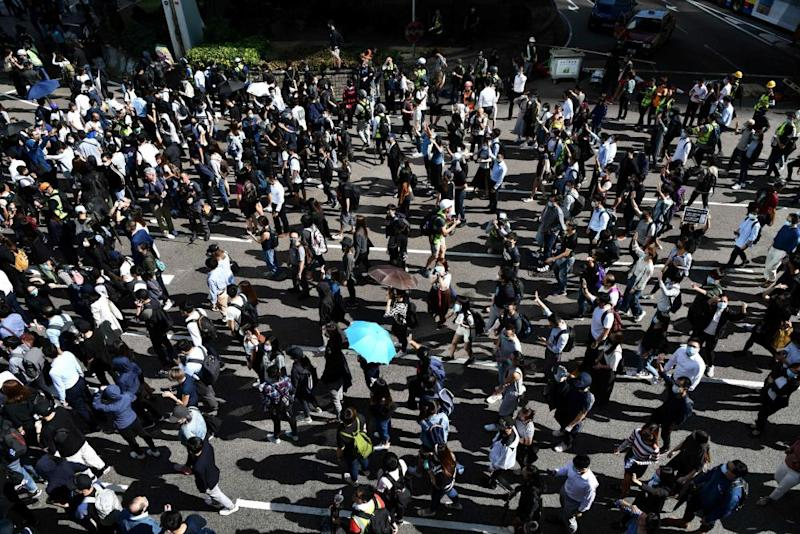 Demonstrators march along a main thoroughfare in Central district