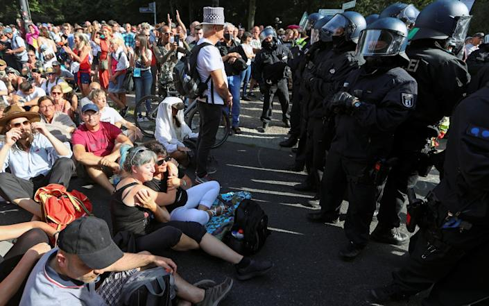 More from Germany: Police officers stand next to demonstrators blocking the street during a protest near the Brandenburg Gate - Reuters