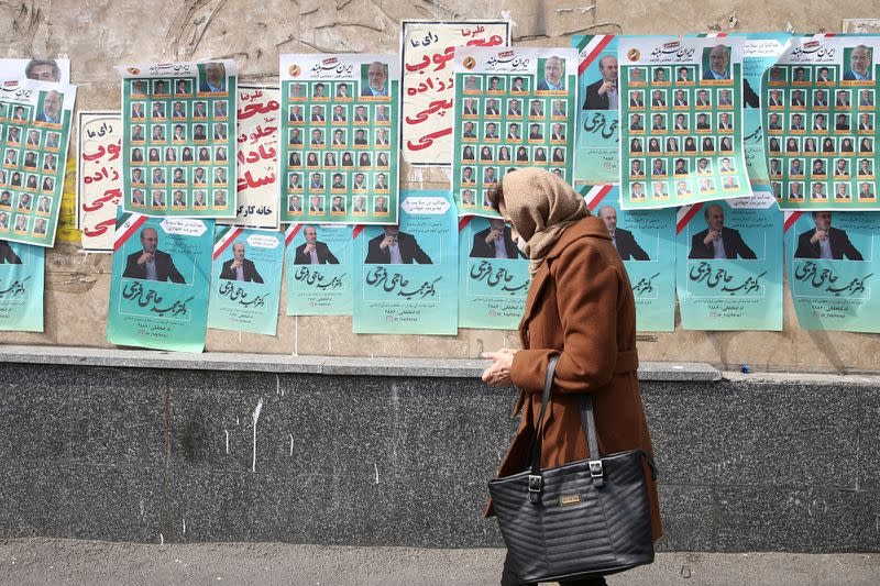 A woman walks past parliamentary election campaign posters in Tehran