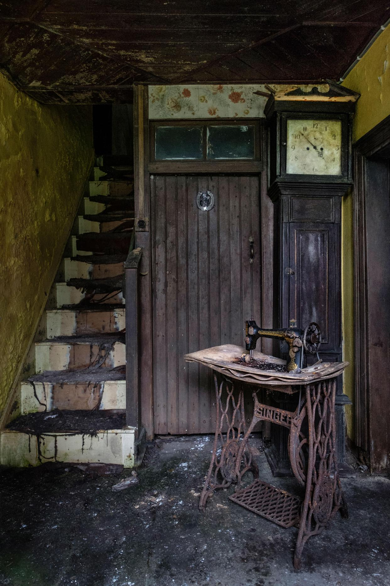 A sewing machine and grandfather clock in a narrow corridor of an abandoned home in Northern Ireland, March 12, 2018. (Photo: Unseen Decay/Mercury Press/Caters News)