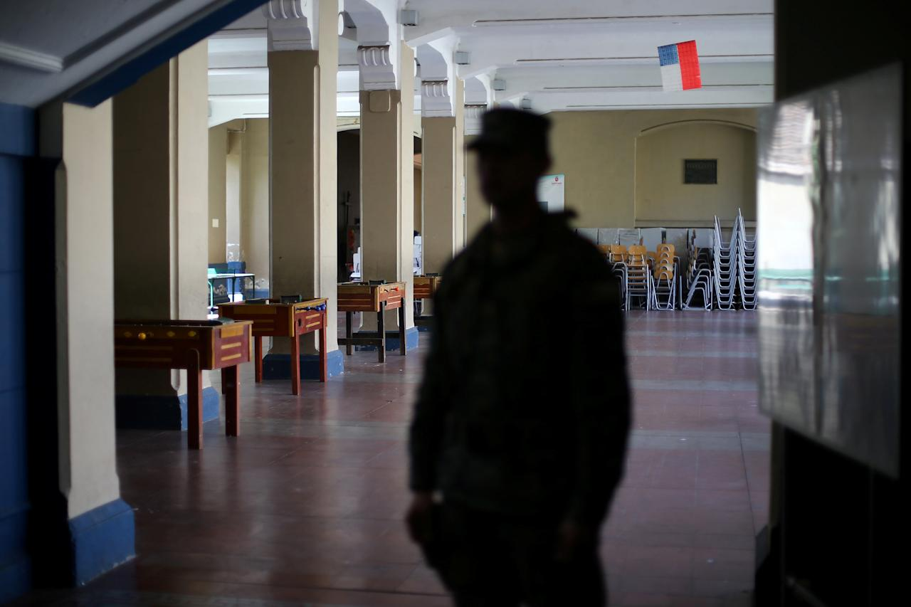 The silhouette of a soldier is seen as he stands guard inside a school that will be used as a voting station for the upcoming mayors and councillors elections in Santiago, Chile, October 21, 2016. REUTERS/Ivan Alvarado