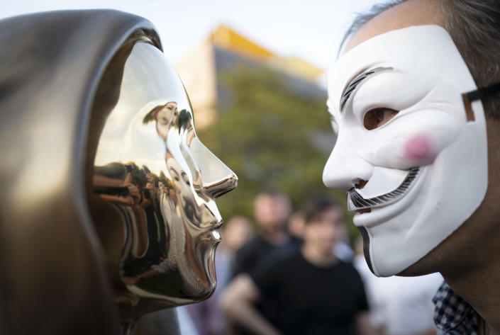 A man wearing a a Guy Fawkes mask looks at a newly unveiled statue of the mysterious developer of the Bitcoin digital currency in Budapest, Hungary, Thursday, Sept. 16, 2021. A bronze statue was unveiled in Hungary's capital on Thursday which its creators say is the first in the world to pay homage to the anonymous creator of the Bitcoin digital currency. Erected in a business park near the Danube River in Budapest, the bust sits atop a stone plinth engraved with the name of Satoshi Nakamoto, the pseudonym of the mysterious developer of Bitcoin whose true identity is unknown. (AP Photo/Bela Szandelszky)