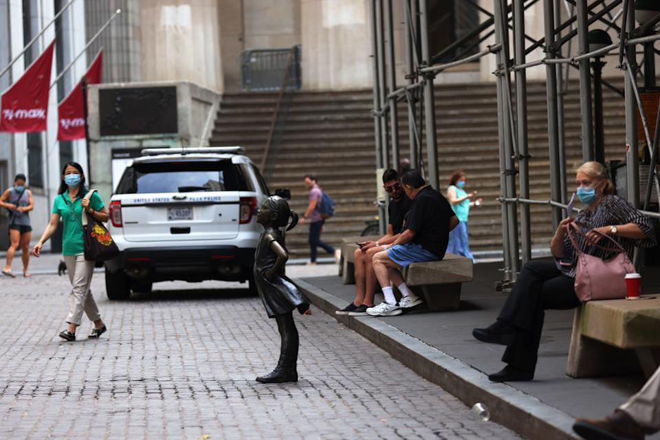 """NEW YORK, NEW YORK - JULY 23: People walk near the """"Fearless Girl"""" statue in front of the New York Stock Exchange (NYSE) at Wall Street on July 23, 2020 in New York City. On Wednesday July 22, the market had its best day in 6 weeks. (Photo by Michael M. Santiago/Getty Images)"""