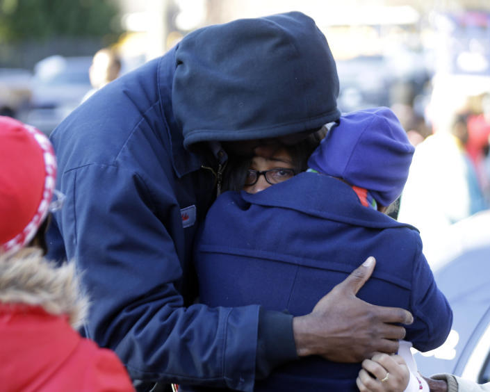 A man and a woman are reunited with a child a child after after a shooting at an Price Middle school in Atlanta Thursday, Jan. 31, 2013. A 14-year-old boy was wounded outside the school Thursday afternoon and a fellow student was in custody as a suspect, authorities said. No other students were hurt. (AP Photo/John Bazemore)