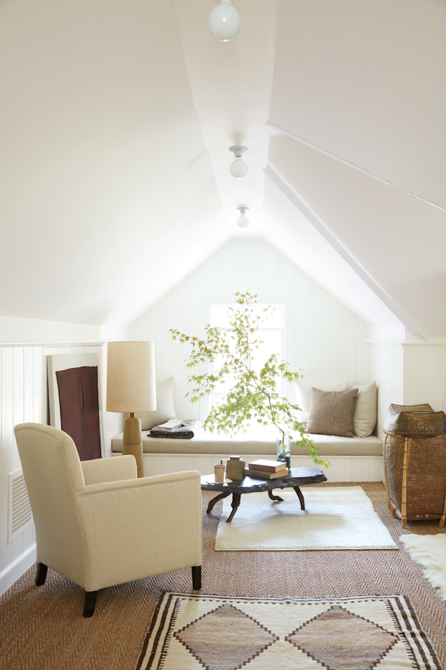 "<p>To unify the interiors of their Connecticut cottage, designers <a href=""http://michaeldeperno.com/"">Michael DePerno</a> and <a href=""https://www.plain-goods.com/"">Andrew Fry</a> covered the walls of each room in a custom blend of Benjamin Moore white paints. The singular hue glows throughout the home including the third-floor design studio. The Herringbone sea-grass rug flawlessly works with the antique armchair, Japanese cocktail table, and Martz lamp to create an inspiring think space.</p>"