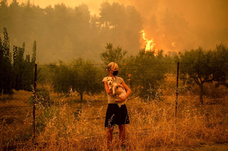 A woman holds a dog in her arms as forest fires approach the village of Pefki on Evia (Euboea) island, Greece's second-largest island, on Aug. 8.