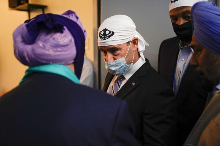 Sen. Todd Young, R-Ind., speaks with members of the Sikh Coalition at the Sikh Satsang of Indianapolis in Indianapolis, Saturday, April 17, 2021, for a commemoration of the victims of the shooting at a FedEx facility in Indianapolis that claimed the lives of four members of the Sikh community. A gunman killed eight people and wounded several others before taking his own life in a late-night attack at a FedEx facility near the Indianapolis airport. (AP Photo/AJ Mast)