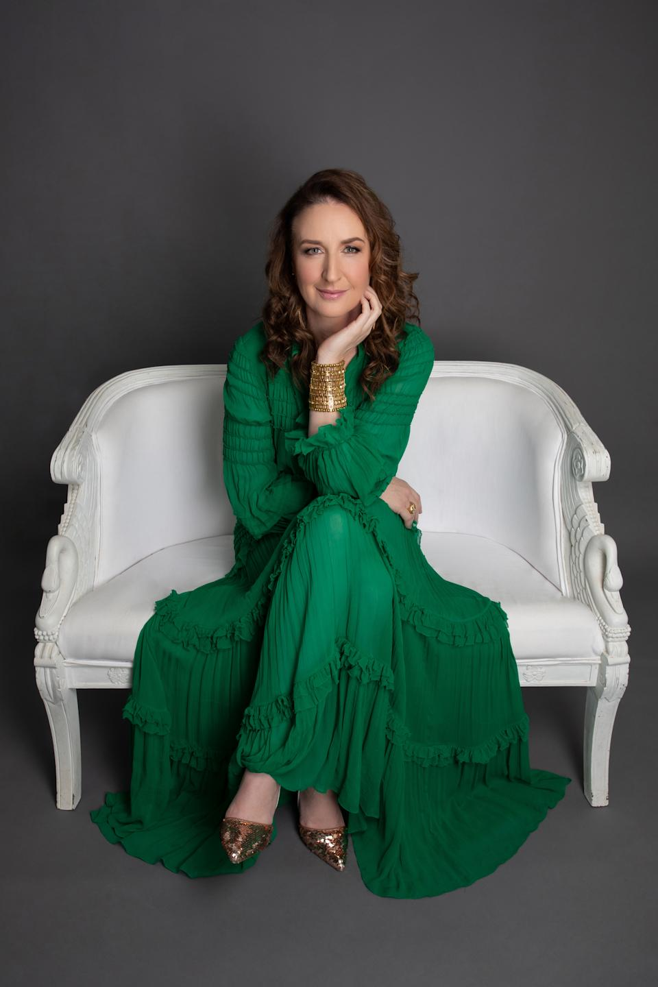 Woman in green dress sitting on a couch