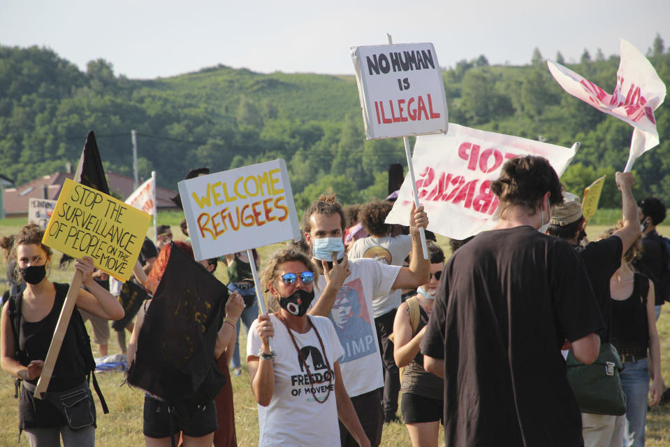 People take part in a protest against the violent pushbacks of migrants, allegedly conducted by Croatian police, near the border crossing between Croatia and Bosnia Herzegovina in Maljevac, Croatia, Saturday, June 19, 2021. More than one hundred members of human rights NGO's, mostly from Italy, but also from Germany, Austria, Spain and Slovenia blocked the border traffic for about two hours protesting demanding a stop of all deportation of migrants, and cancellation of EU's Frontex operations at borders, preventing migrants from traveling. (AP Photo/Edo Zulic)