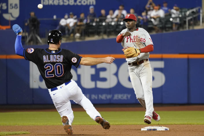 Philadelphia Phillies shortstop Didi Gregorius, right, throws to first to complete a double play after forcing out New York Mets' Pete Alonso (20) off a hit by Michael Conforto during the sixth inning of a baseball game, Friday, Sept. 17, 2021, in New York. (AP Photo/Mary Altaffer)