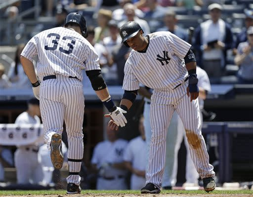 New York Yankees Robinson Cano greets New York Yankees designated hitter Travis Hafner (33) at the plate after scoring on Hafner's first-inning, three-run home run in a baseball game at Yankee Stadium in New York, Wednesday, June 5, 2013. (AP Photo/Kathy Willens)