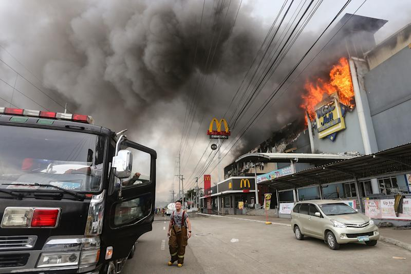 A firefighter stands in front of the NCCC Mall in Davao on the southern Philippine island of Mindanao. (MANMAN DEJETO via Getty Images)