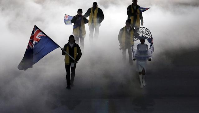 Peter Crooks of the British Virgin Islands holds his country's national flag and enters with his team during the opening ceremony of the 2014 Winter Olympics in Sochi, Russia, Friday, Feb. 7, 2014. (AP Photo/Charlie Riedel)