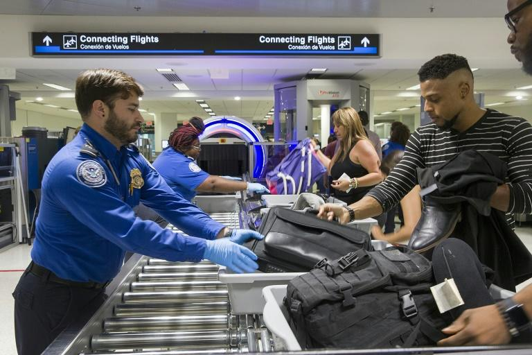 TSA agents help travelers pass their bags through the 3-D scanner at the Miami International Airport in May 2019