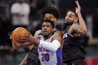 Detroit Pistons guard Josh Jackson (20) drives to the basket as Sacramento Kings forward Marvin Bagley III, left, and guard Cory Joseph defends during the second half of an NBA basketball game, Friday, Feb. 26, 2021, in Detroit. (AP Photo/Carlos Osorio)
