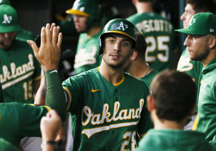 Oakland Athletics' Matt Olson is greeted in the dugout after hitting a solo home run against the Texas Rangers during the fourth inning of a baseball game in Arlington, Texas, Sunday, July 11, 2021. (AP Photo/Ray Carlin)