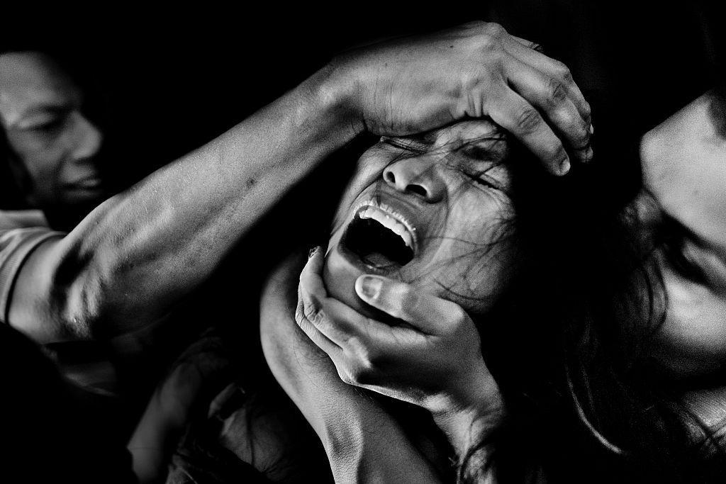A girl screams while being allegedly possessed by demons during an exorcism ritual performed in Colombia. (Photo: Jan Sochor via Getty Images)