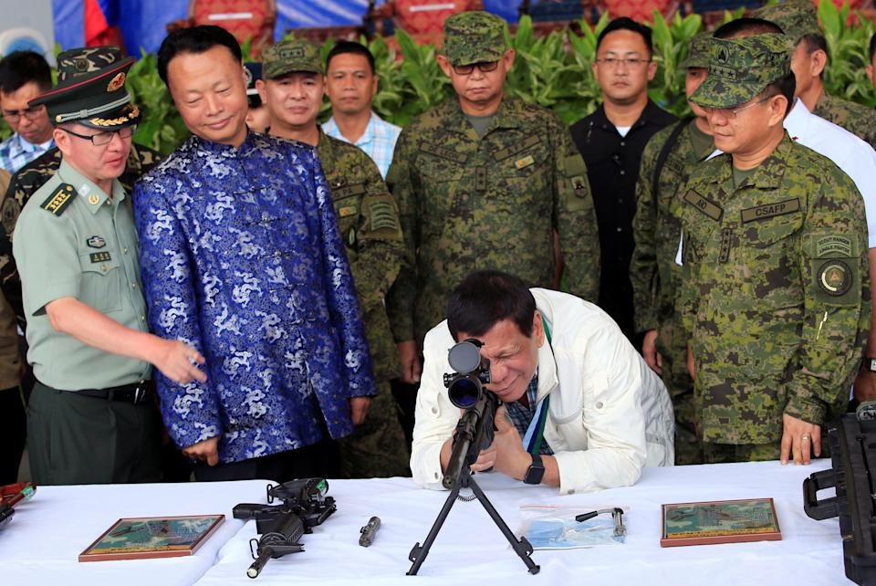 FILE PHOTO: Philippine President Rodrigo Duterte checks the scope of a 7.62mm sniper rifle during the turnover ceremony of China's urgent military assistance given