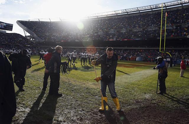 Grounds keepers prepare the field to resume play after a severe storm blew through Soldier Field and suspended play during the first half of an NFL football game between the Chicago Bears and Baltimore Ravens, Sunday, Nov. 17, 2013, in Chicago. (AP Photo/Charles Rex Arbogast)