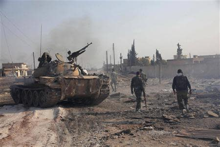 Forces loyal to Syria's President Bashar al-Assad hold their weapon as they stand near a tank in Tel Hasel, Aleppo province after capturing it from rebels
