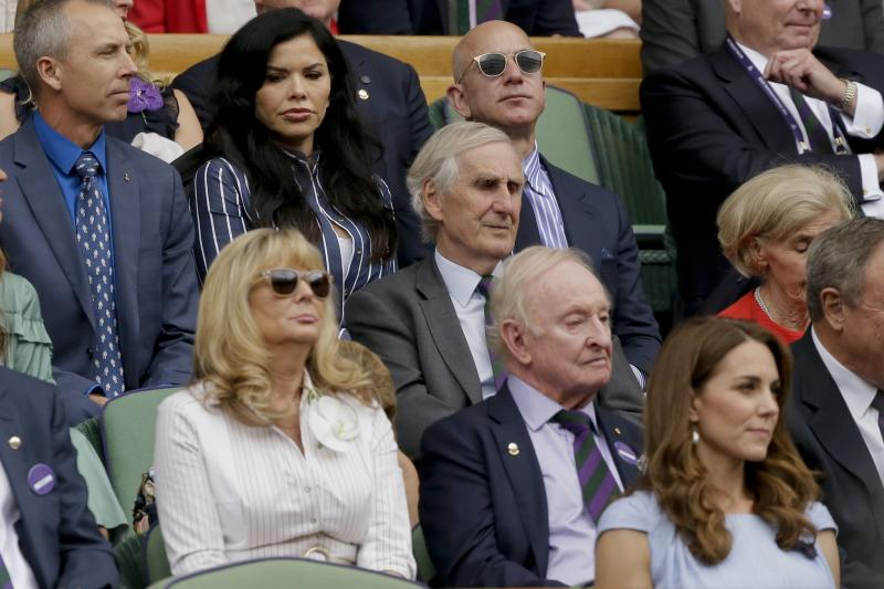 Amazon founder Jeff Bezos, top and third from left, and Lauren Sanchez, top and second from left, sit in the Royal Box on Centre Court to watch the men's singles final match of the Wimbledon Tennis Championships in London, Sunday, July 14, 2019. (AP Photo/Tim Ireland)