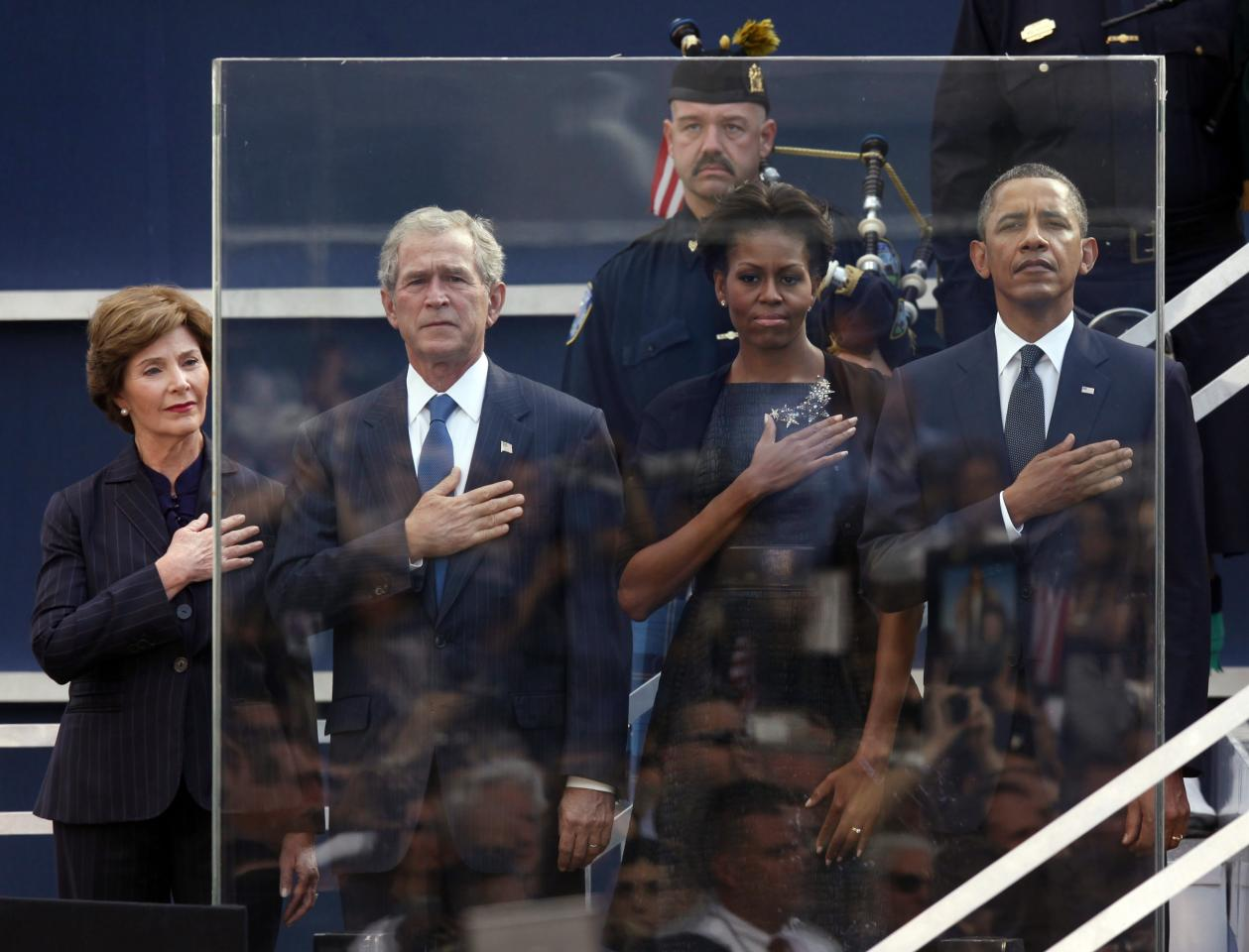 Former first lady Laura Bush, from left, former President George W. Bush, first lady Michelle Obama and President Barack Obama hold hands to their hearts during the national anthem as friends and relatives of the victims of 9/11 gather for a ceremony marking the 10th anniversary of the attacks at the National September 11 Memorial at the World Trade Center site, Sunday, Sept. 11, 2011, in New York. (AP Photo/Jason DeCrow)