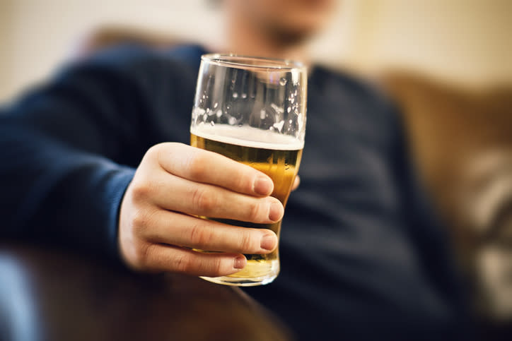 A man is pictured holding a pint of beer.