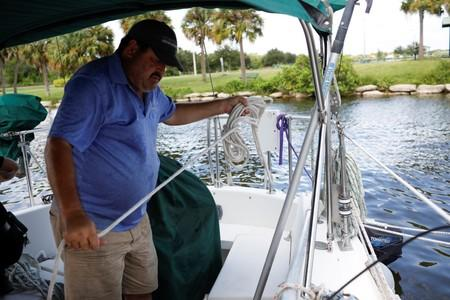 Ned Keahey, who lives in a sailboat with his wife Lisa and plans to stay aboard during Hurricane Dorian, secures his sailboat at a marina in Titusville