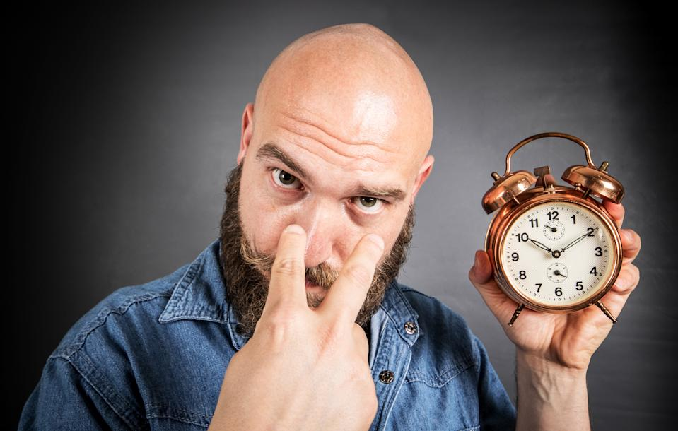 Bearded man holding an alarm clock looking at the user.