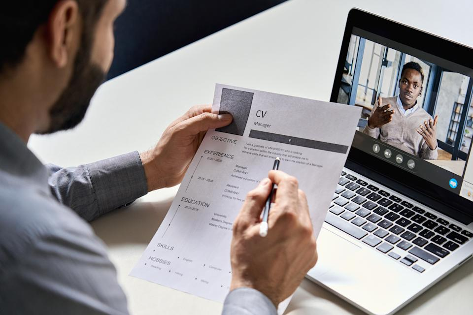 Male indian hr, recruiter or employer holding cv having online virtual job interview meeting with african candidate on video call. Distance remote recruitment conference chat. Over shoulder view.