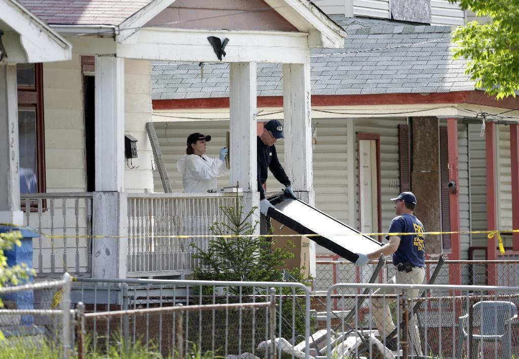 Law enforcement officials gather evidence at the crime scene where three women were held captive in Cleveland, Ohio, Thursday, May 9, 2013. Ariel Castro, a 52-year-old former school bus driver, is being held on $8 million bail under a suicide watch in jail, where he is charged with rape and kidnapping for allegedly abducting three women and holding them captive in his home for a decade. (AP Photo/David Duprey)