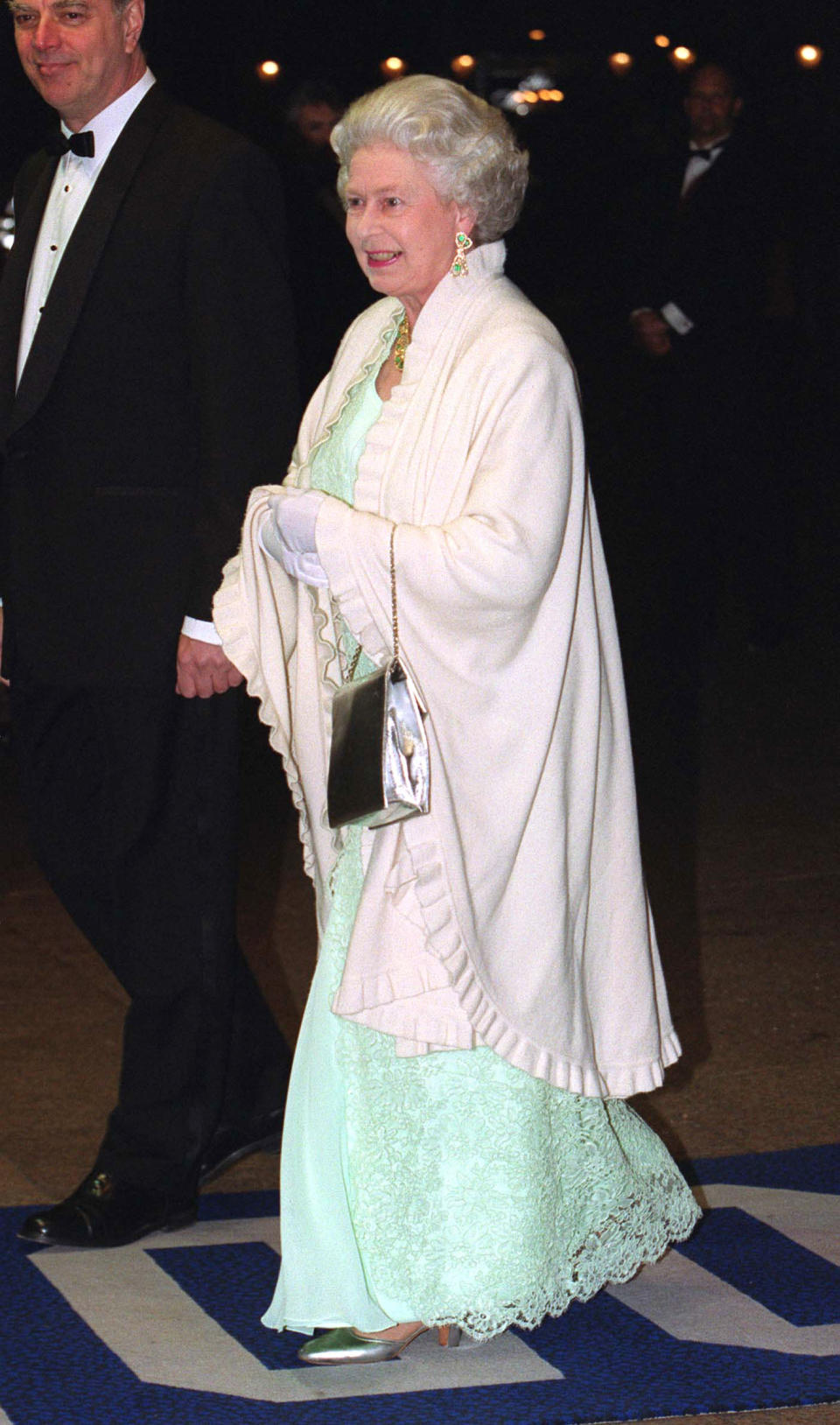 <p>Her Majesty dressed in a festive green dress complete with metallic accessories back in the year 2000. <em>[Photo: Getty]</em> </p>