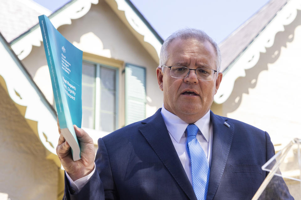 Picture of Prime Minister Scott Morrison holding up Aged Care Royal Commission final report