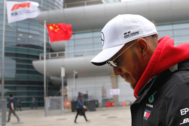 """FILE - In this April 12, 2018 file photo, Mercedes driver Lewis Hamilton of Britain walks at the paddock of the Shanghai International Circuit ahead of the Chinese Formula One Grand Prix in Shanghai. More Formula One races are coming to Asia, and a street race in the Vietnamese capital Hanoi could be the first addition. Formula One's managing director of commercial operations tells The Associated Press that Hanoi could be added for the 2020 season, though there has been some speculation it could arrive as early as next season. Sean Bratches says a second race in China is also likely and would join Shanghai. He says deciding where will """"be left to local Chinese partners."""" (AP Photo/Andy Wong, File)"""