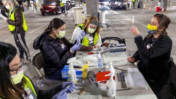 PHOTO: Medical professionals from Oregon Health & Science University load syringes with the Moderna COVID-19 vaccine at a drive-thru vaccination clinic in Portland, Ore., Jan. 10, 2021. (Kristyna Wentz-Graff/Pool via AP)