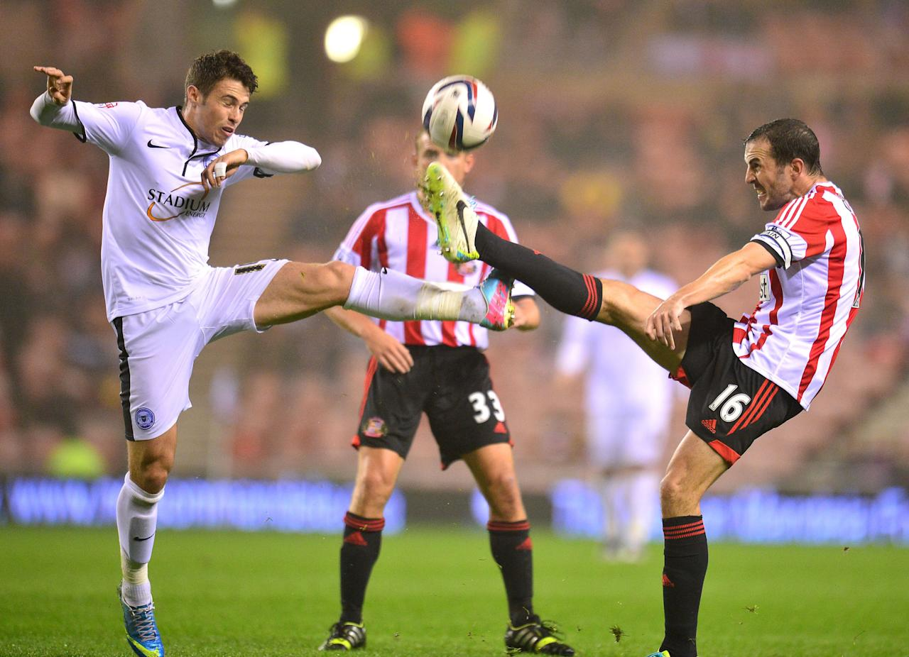 Sunderlands John O'Shea (right) and Peterborough's Tommy Rowe battle for the ball during the Capital One Cup, Third round match at the Stadium of Light, Sunderland.