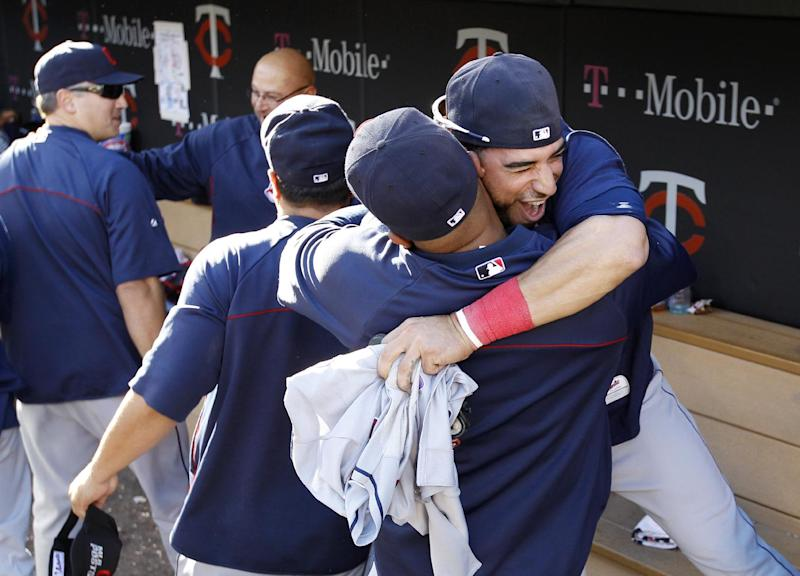Cleveland Indians shortstop Mike Aviles jumps into the arms of a teammate as the celebrate in the dugout after the Indians beat the Twins 5-1 to clinch a wild card spot in the playoffs in a baseball game in Minneapolis, Sunday, Sept. 29, 2013. (AP Photo/Ann Heisenfelt)