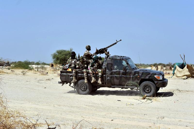 Niger soldiers ride in a military vehicle on May 25, 2015 in Malam Fatori, in northern Nigeria, near the border with Niger