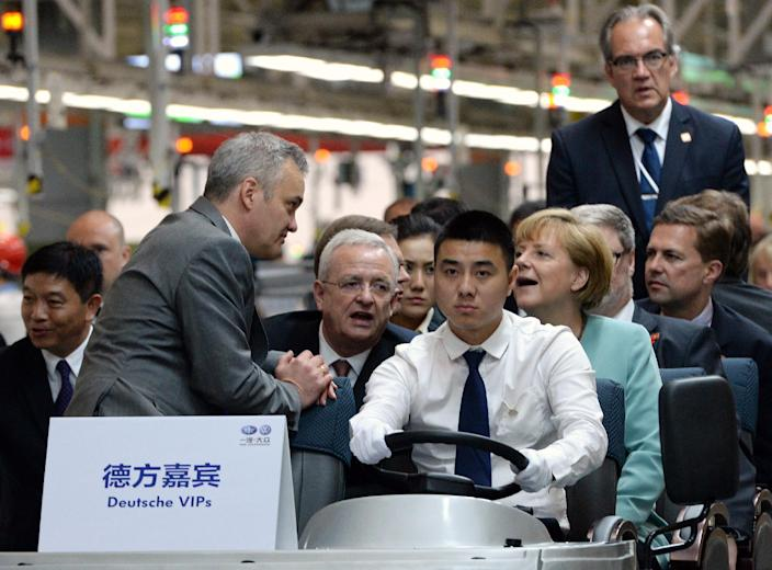 Angela Merkel and her delegation ride an electric vehicle during a visit to the FAW-Volkswagen plant in Chengdu, southwest China's Sichuan province on July 6, 2014 (AFP Photo/Goh Chai Hin)
