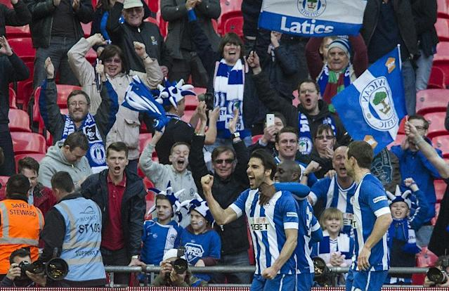 Wigan Athletic's Jordi Gomez, left, celebrates with teammates after scoring against Arsenal, during their English FA Cup semifinal soccer match, at the Wembley Stadium in London, Saturday, April 12, 2014. (AP Photo/Bogdan Maran)
