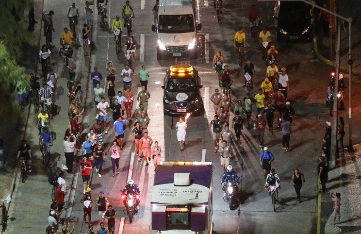 A runner carries the Olympic torch as security and onlookers follow. (Getty Images)