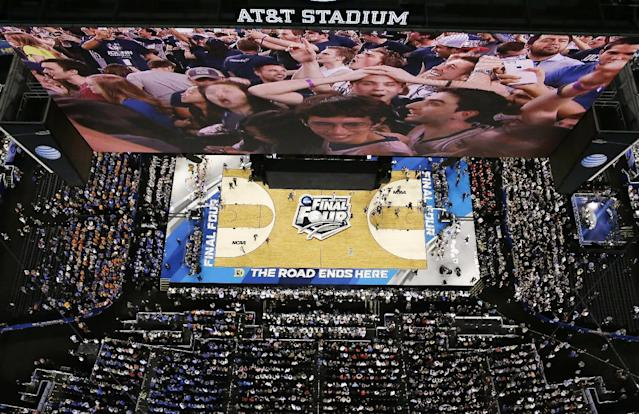 Connecticut fans are shown on the stadium scoreboard as they celebrate after an NCAA Final Four tournament college basketball semifinal game against Florida Saturday, April 5, 2014, in Arlington, Texas. Connecticut won 63-53. (AP Photo/David J. Phillip)