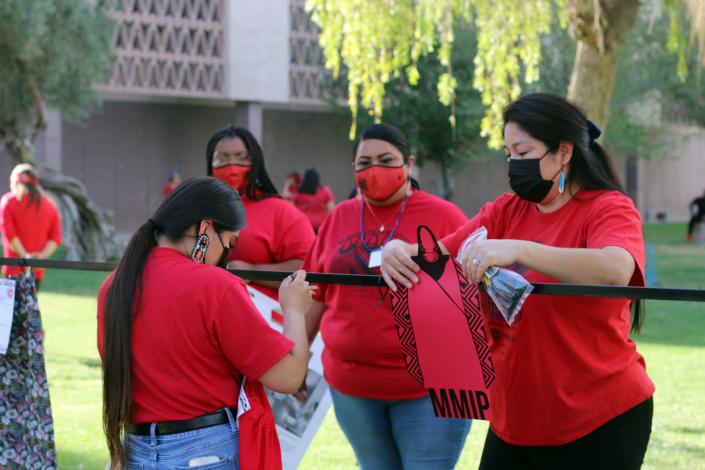 Volunteers and members of the Phoenix Indian Center hang up red skirts designed by artists to raise awareness for missing and murdered Indigenous women and girls, at Arizona State Capitol in Phoenix, Wednesday, May 5, 2021. Phoenix Indian Center Executive Director Patricia Hibbeler said the skirts are a huge part of Native American women and girls' lives. (AP Photo/Cheyanne Mumphrey)