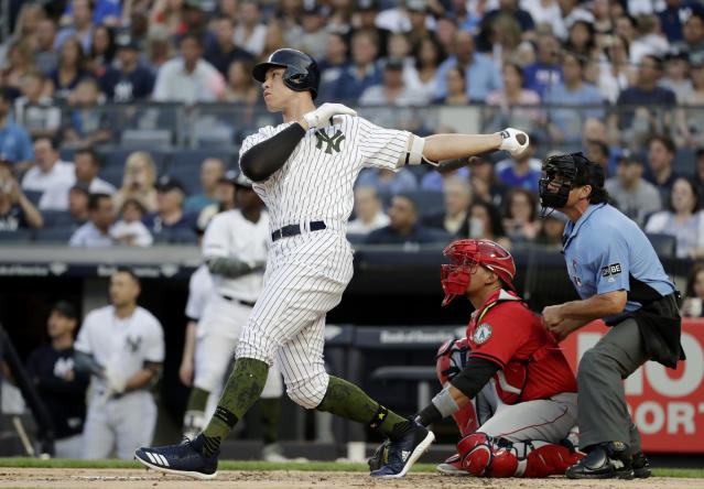 New York Yankees' Aaron Judge follows through on a home run off Los Angeles Angels starting pitcher Jaime Barria as Angels catcher Jose Briceno, center, and home plate umpire Phil Cuzzi watch during the first inning of a baseball game Saturday, May 26, 2018, in New York. (AP Photo/Julio Cortez)