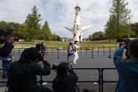 Former Olympian Aya Terakawa, center, participating as an Olympic torch relay runner, waves as she carries the torch during the first day of the Osaka round at a former Expo site in Suita, north of Osaka, western Japan, Tuesday, April 13, 2021. The Tokyo 2020 Olympic kick-off event which was rescheduled due to the coronavirus outbreak was yet rearranged to hold at the former Expo park, instead of public streets, to close off the audience from the even, following the mayor's decision as Osaka has had sharp increases in daily cases since early March. (AP Photo/Hiro Komae)