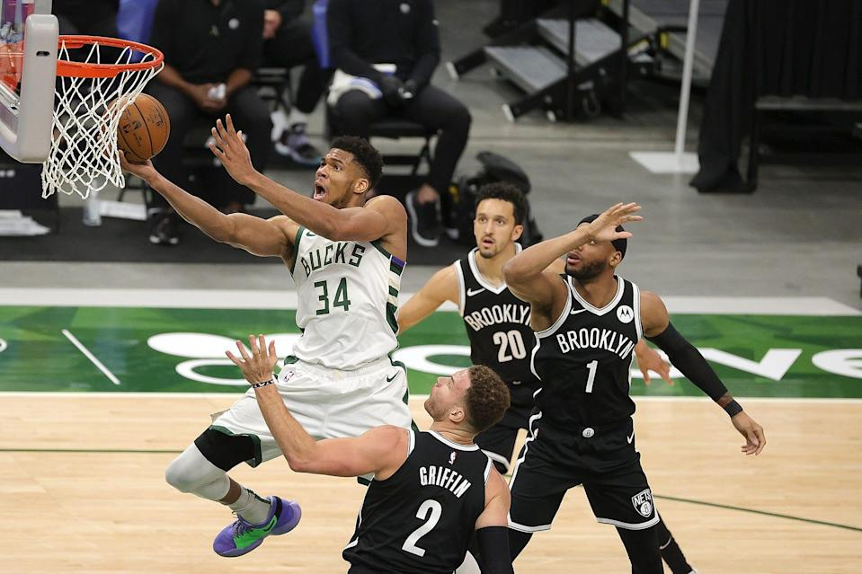 The Bucks' Giannis Antetokounmpo soars past the Nets' Blake Griffin (2) during the second half.