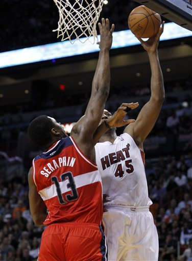 Miami Heat's Dexter Pittman (45) goes to the basket as Washington Wizards' Kevin Seraphin (13) defends in the first half of an NBA basketball game in Miami, Saturday, April 21, 2012. (AP Photo/Alan Diaz)