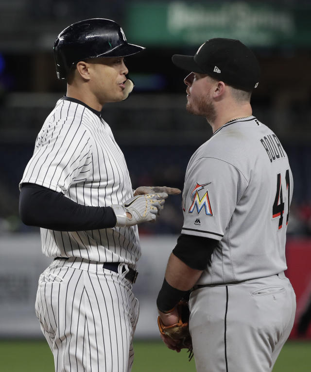 New York Yankees' Giancarlo Stanton, left, speaks with Miami Marlins first baseman Justin Bour (41) after walking during the fourth inning of a baseball game, Monday, April 16, 2018, in New York. (AP Photo/Julie Jacobson)