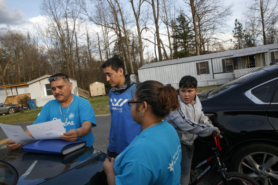 """Prisi Hernandez, left, and Laura Hernandez, both with the organization Siembra NC, help Nery Ocampo, 19, center, to register to vote, as Irvin Bahena, 10, stops to watch from his bicycle, in a largely Latino trailer community in Burlington, N.C., Wednesday, March 11, 2020. It will be Ocampo's first time voting. voting. """"I didn't have time to register before,"""" says Ocampo, """"it's important for Latinos who can to vote, in order to help those who can't."""" (AP Photo/Jacquelyn Martin)"""