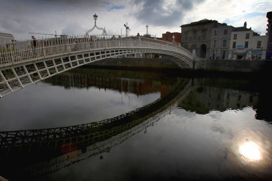 A view of the Ha'penny Bridge over the Liffey River in Dublin, Ireland.